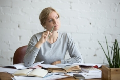 Portrait of a student woman sitting at the desk, frowned, looking aside lifestyle. Education concept photo