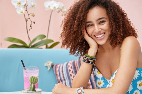 Positive dark skinned curly female with broad smile enjoys good recreation in cafeteria, drinks cocktail while sits on comfortable couch against pink wall with orchid in background, has rest